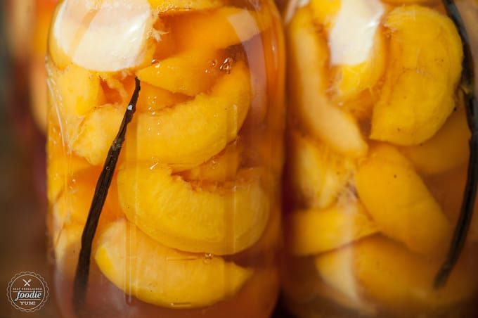 a close up of canned peaches with vanilla bean