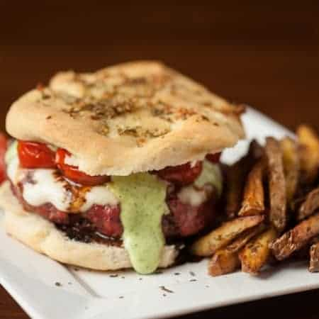 These amazing Caprese Burgers have everything a mouthwatering burger should have - homemade basil garlic aioli, roasted tomatoes, and balsamic reduction.