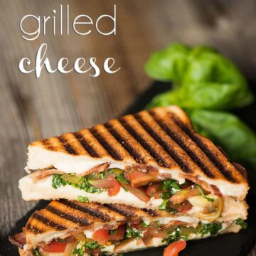 two caprese grilled cheese half sandwiches stacked on top of each other
