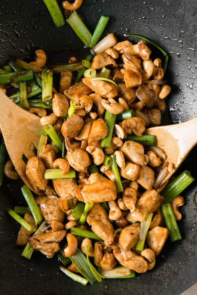 Cashew Chicken in wok with wooden spoons