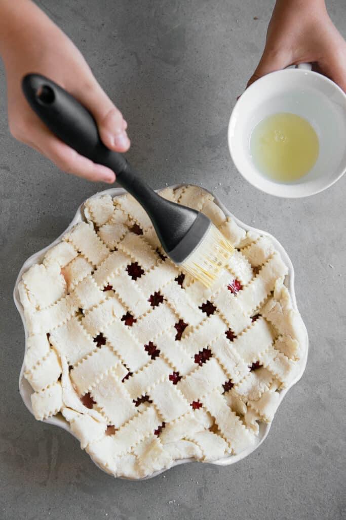 pastry brush applying egg white to fruit pie