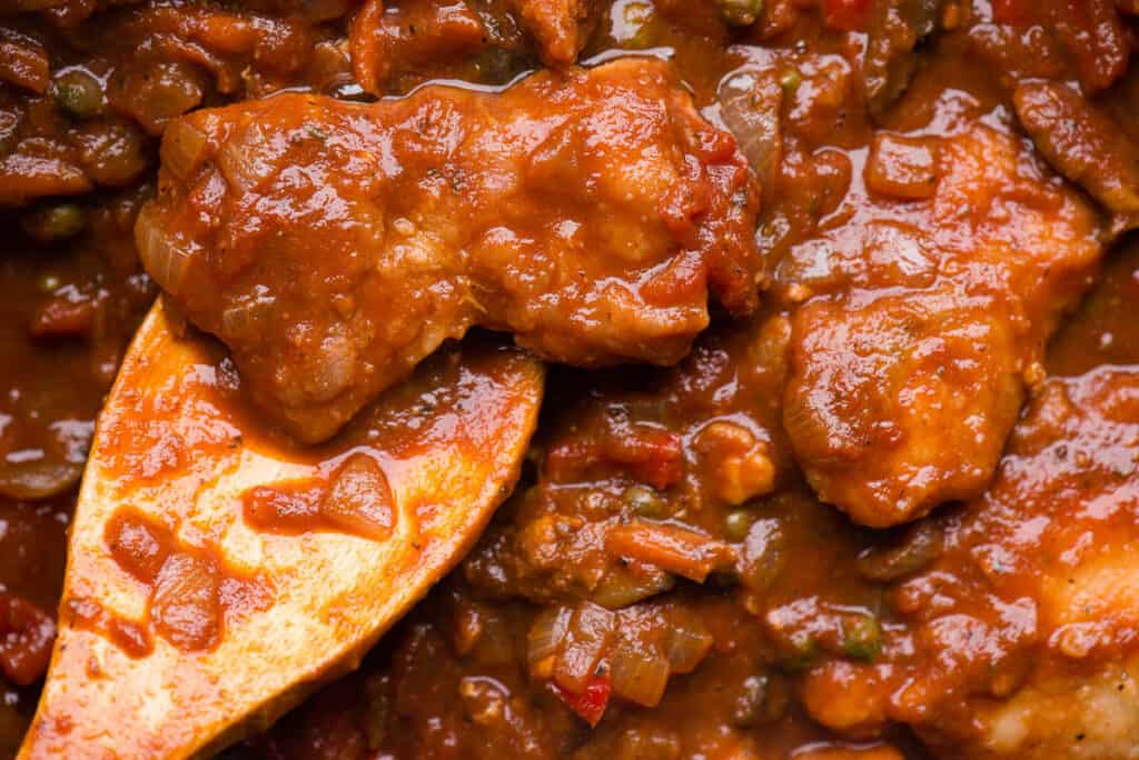 close up of chicken thigh cooked in tomato stew