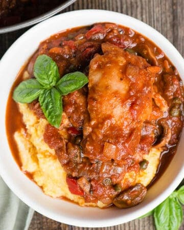 white bowl with polenta and chicken stew in tomato sauce