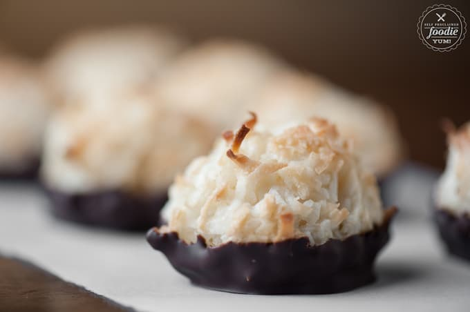 side view of a homemade coconut macaroon with the bottom dipped in chocolate