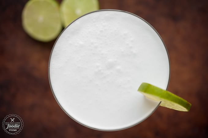 Top of a homemade coconut lime blended daiquiri garnished with lime slices