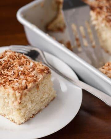 A slice of coconut poke cake on plate