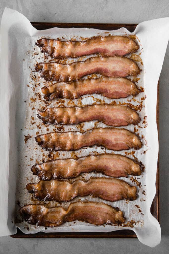 partially cooked bacon slices on parchment lined baking sheet