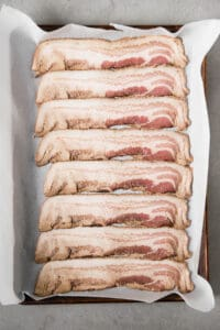 uncooked bacon slices on baking sheet