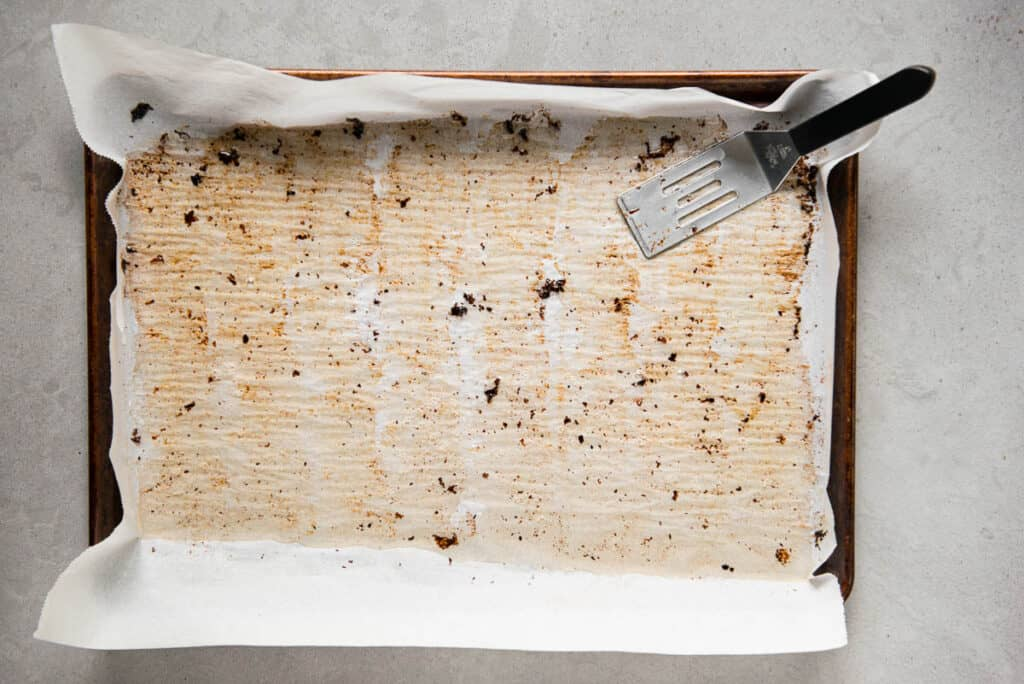 bacon grease with spatula on parchment paper