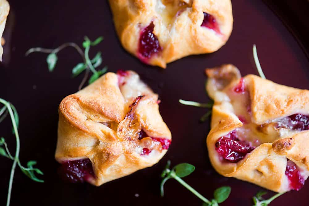 Easy 3-ingredient appetizers with cranberry sauce, brie, and cresent roll dough.