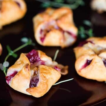 Cranberry Brie Bites are an easy three ingredient appetizer that are perfect for holiday parties. Warm and delicious - everyone will love them!