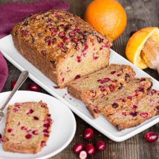 homemade cranberry orange bread with slice on plate
