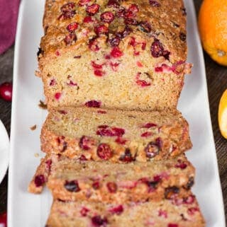 sliced quick bread with orange and cranberry on white platter