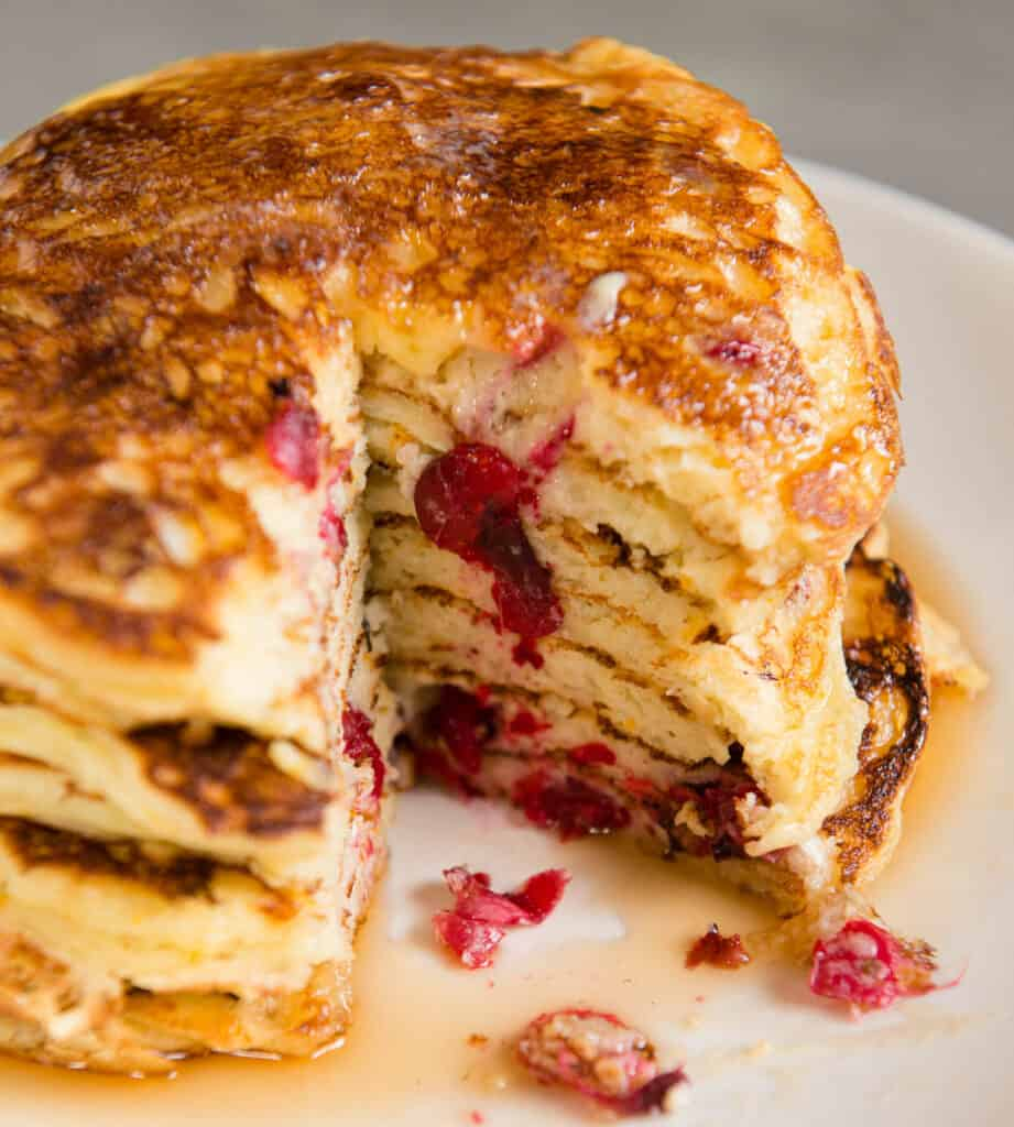 huge stack of cranberry Buttermilk Pancakes with a bite cut out