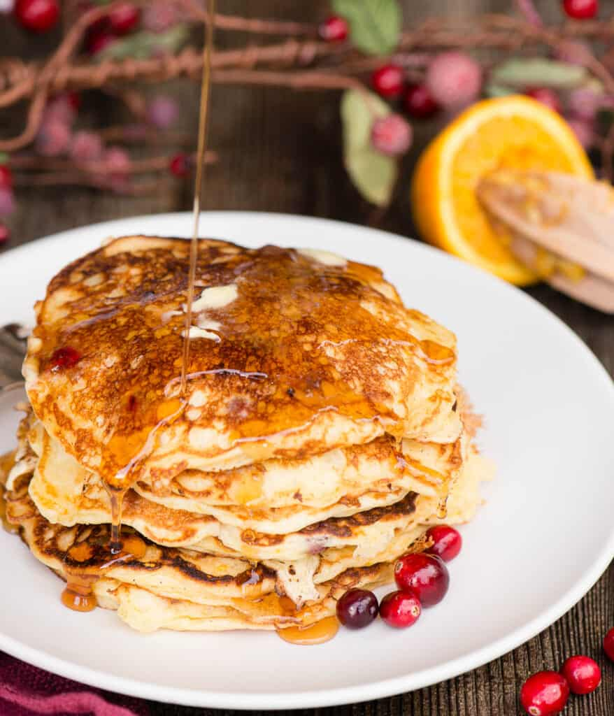 stack of cranberry Buttermilk Pancakes with a stream of syrup