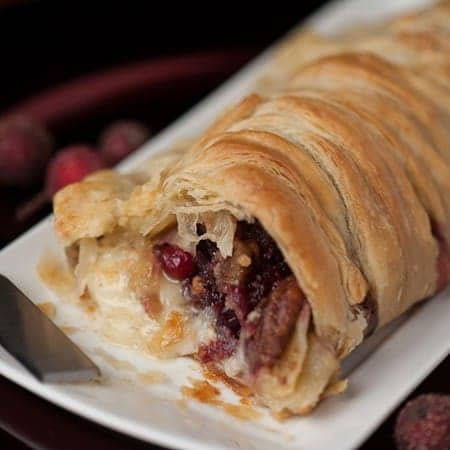Warm Cranberry Pecan Brie en Croute wraps buttery puff pastry around brie, fresh cranberry sauce, and candied pecans to make the perfect holiday appetizer.