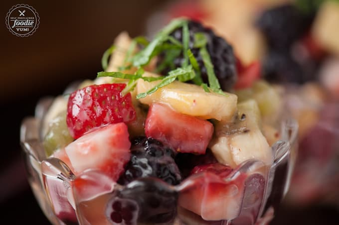 A close up of fruit salad with lemon curd dressing and sliced mint
