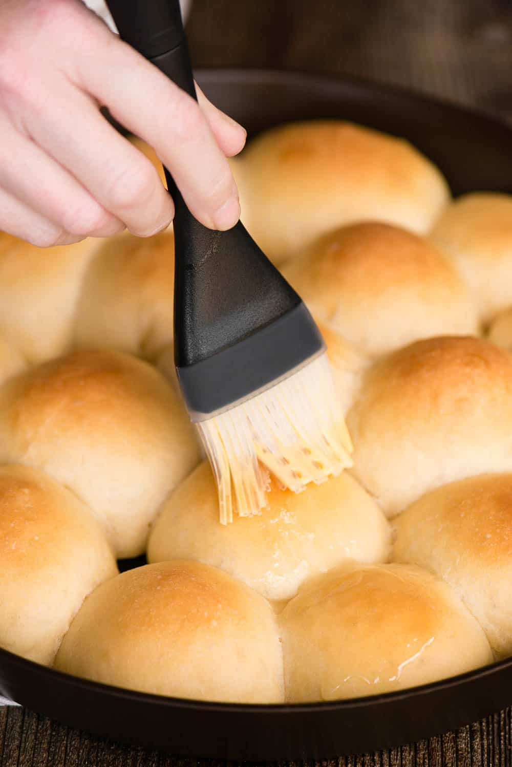 spreading melted butter on yeast bread rolls