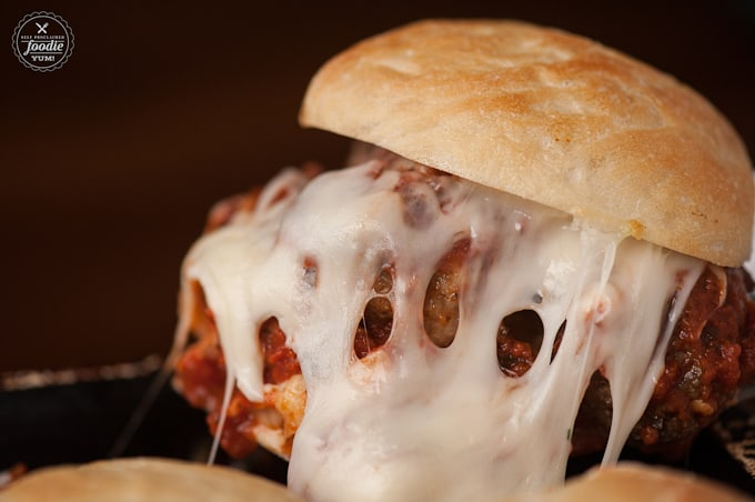 stuffed meatball slider sandwich with marinara sauce and lots of melted cheese
