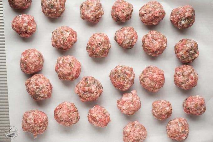 uncooked stuffed meatballs on baking sheet