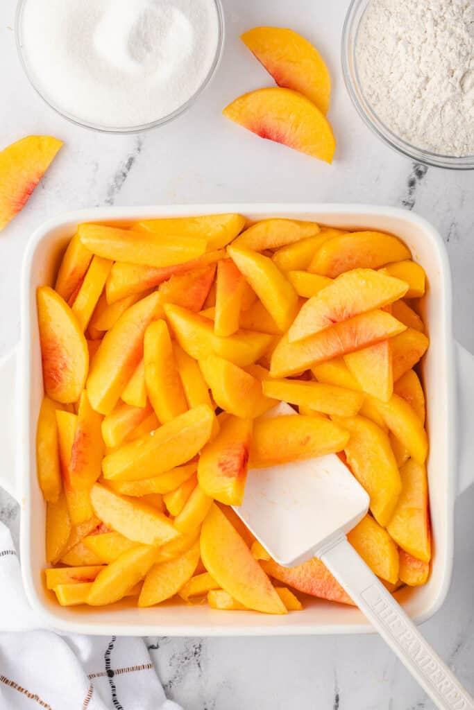 fresh peach slices in baking dish