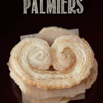 looking down at a stack of Palmier cookies separated with parchment paper