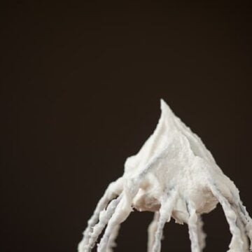 a close up of eggnog frosting on a whisk