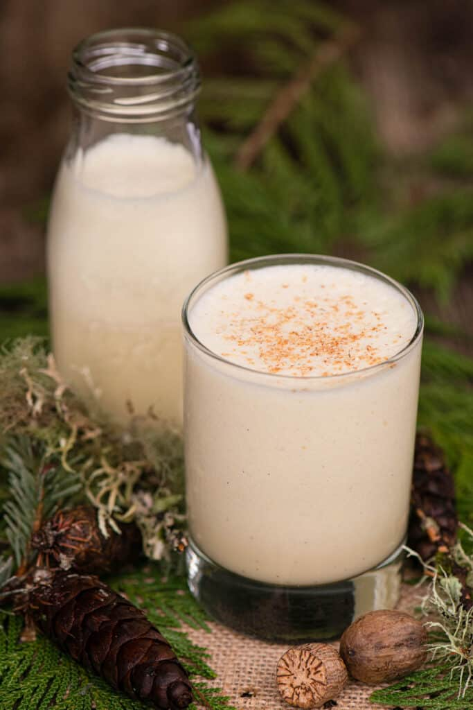 homemade eggnog in glass with festive holiday decor