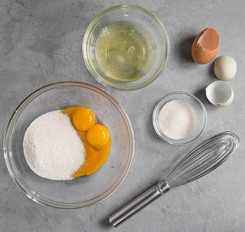 separated eggs in bowls with sugar