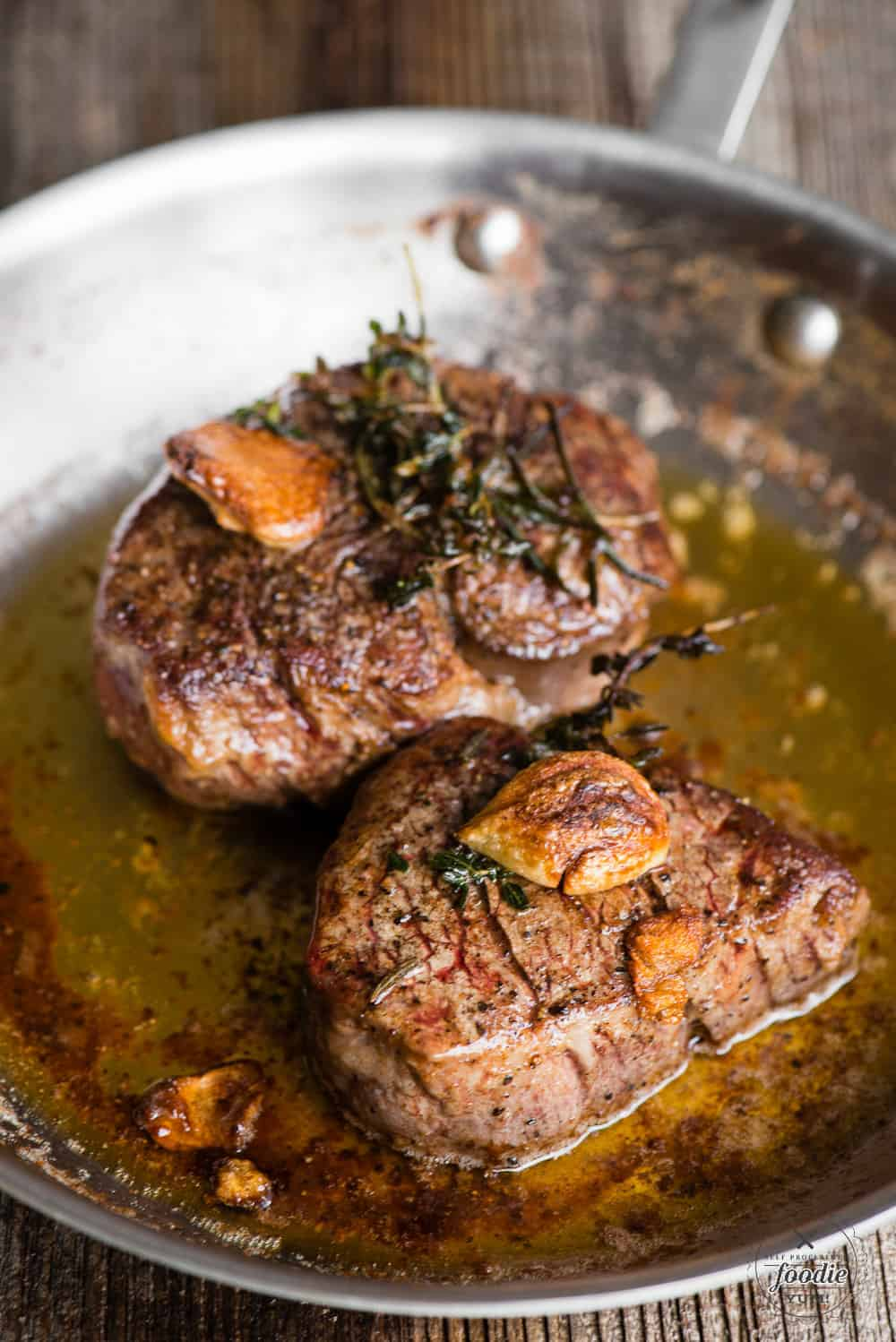 tenderloin steak in pan with garlic herb butter