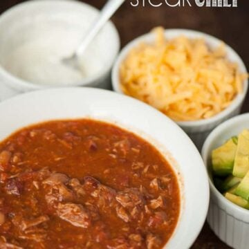 Steak Chili in bowl with sour cream, cheese, and avocado