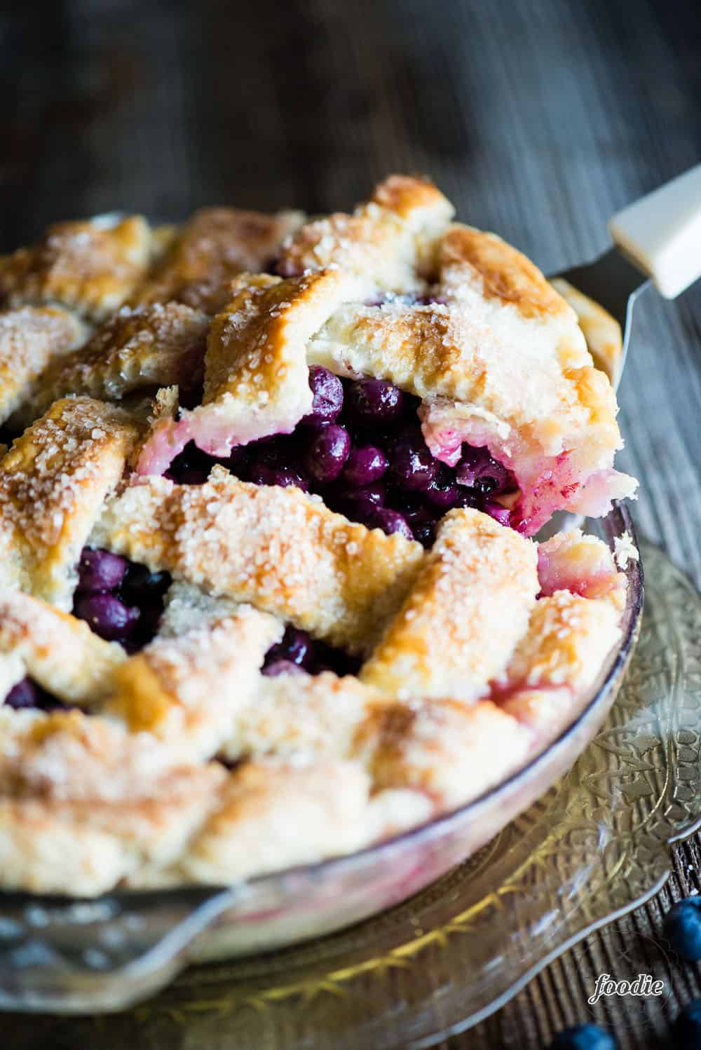 lifting a slice of fresh blueberry pie out of the pie dish