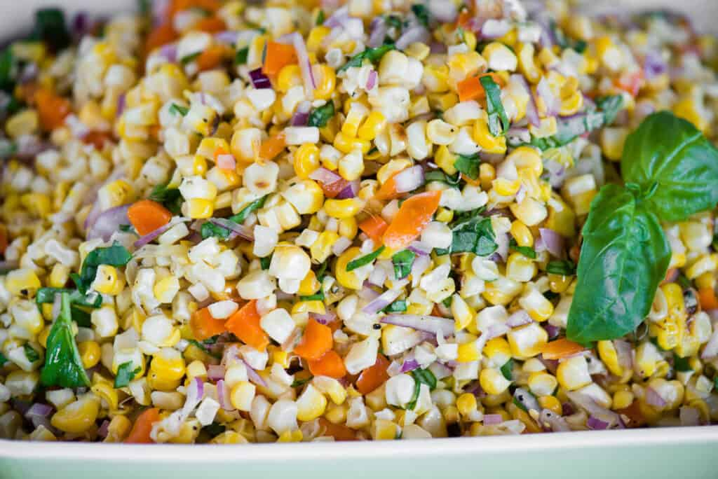 close up of grilled corn with onions, peppers, and basil