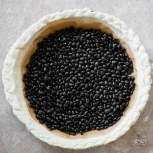 pie crust weighted down with dry black beans