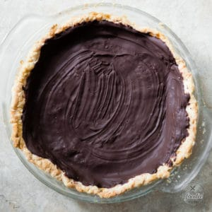cooked pie crust with a layer of chocolate