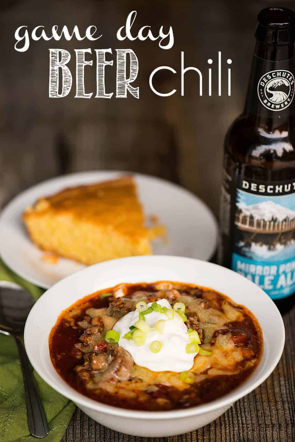 bowl of chili with a side of corn bread and a bottle of beer