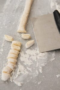 pastry cutter cutting pieces of homemade gnocchi