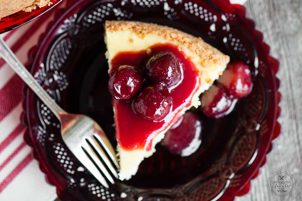 slice of homemade classic cheesecake with cherry topping