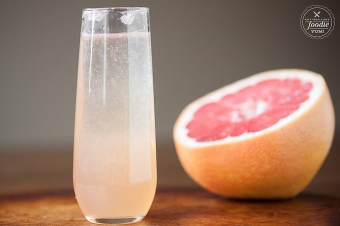 glass of grapefruit champagne cocktail with half of a pink grapefruit in background