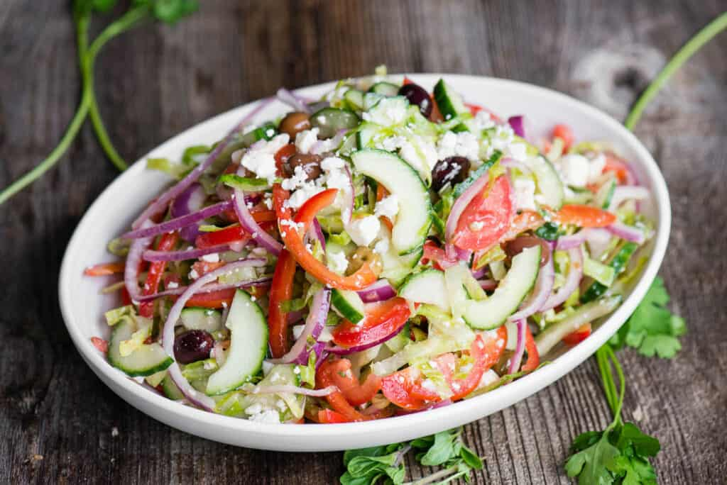 homemade Greek Salad in white oval dish