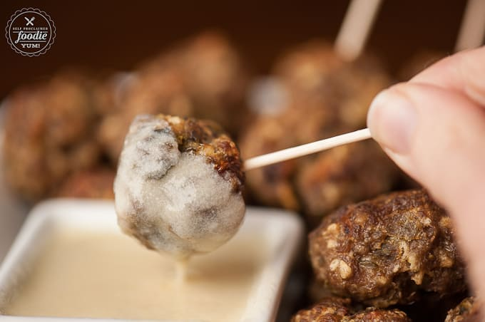 Green Chile Cheddar Meatball on toothpick dipped in white cheddar cheese sauce