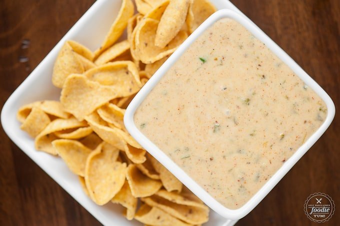 square white dish of cheese sauce with chips