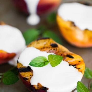 four grilled peach halves with sweet cream
