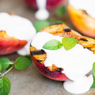 half of a grilled peach with sweetened cream on top