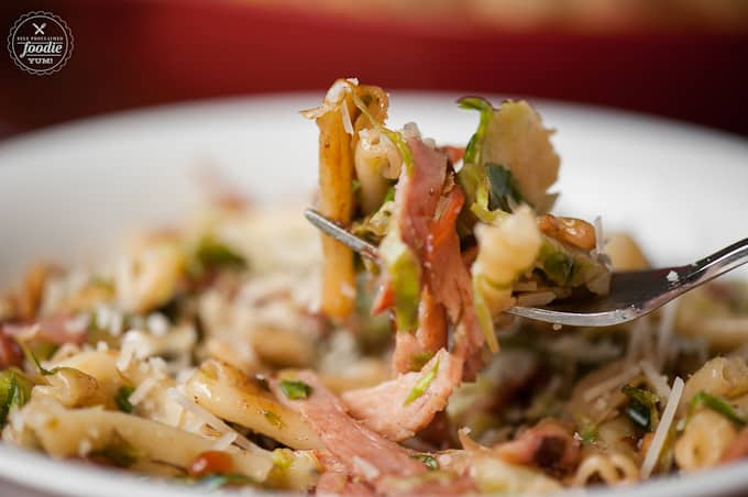 a fork with pasta, ham and brussels sprouts