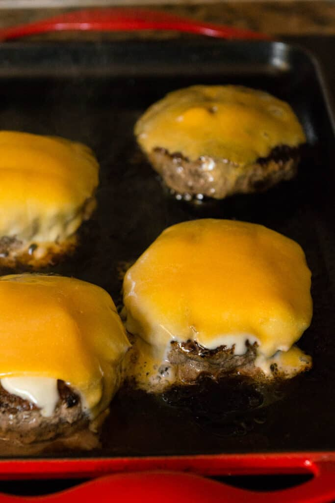 burger patties with melted cheese on griddle