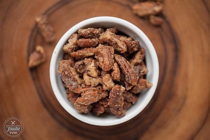 A close up of a bowl of candied pecans on a plate