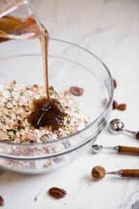 pouring honey into homemade granola