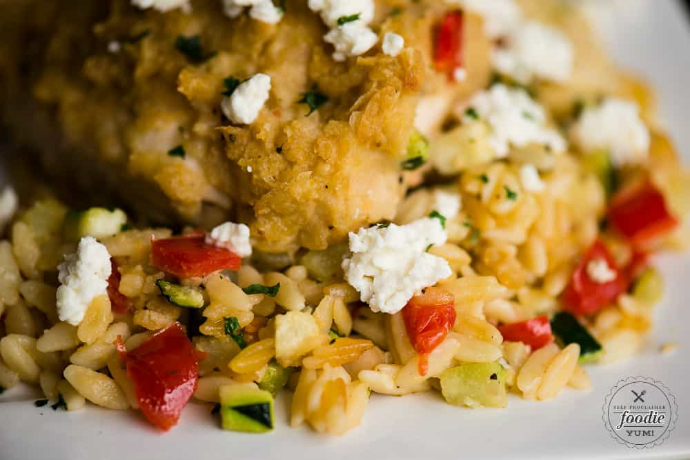 A close up of hummus baked chicken with feta and vegetable orzo