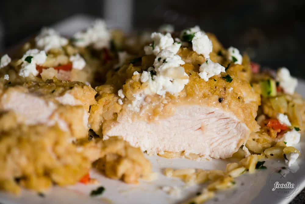 a cut piece of hummus baked chicken with feta and vegetable orzo